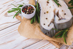 Raw fresh white fish steak with rosemary and seasoning Royalty Free Stock Photos