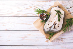 Raw fresh white fish steak with rosemary and seasoning Royalty Free Stock Photography