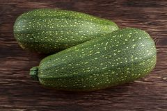 Raw Freshly picked organic marrow zucchini vegetables with leaves on wooden table.  Stock Photos