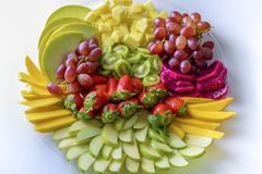 Raw fruits assortment platter on the white plate, on the white table. stock photo