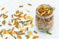 Raw fusilli pasta on a glass jar. On blue wood table Stock Image