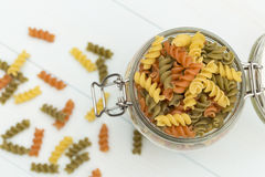 Raw fusilli pasta on a glass jar. On blue wood table Royalty Free Stock Photos