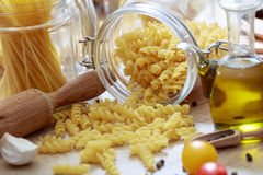 Raw fusilli pasta, tomatoes and olive oil. Raw fusilli pasta, tomatoes, olive oil and a rolling pin Stock Image