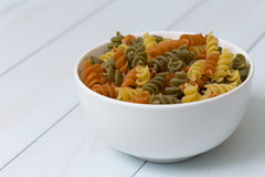 Raw fusilli pasta in a white bowl. On blue wood table Stock Images