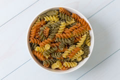Raw fusilli pasta in a white bowl. On blue wood table Stock Image