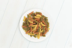 Raw fusilli pasta in a white plate. On blue wood table Royalty Free Stock Photography