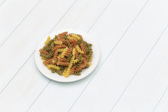 Raw fusilli pasta in a white plate. On blue wood table Stock Image