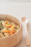 Raw fusilli pasta on wooden bowl Stock Photo