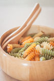 Raw fusilli pasta on wooden bowl Stock Photos