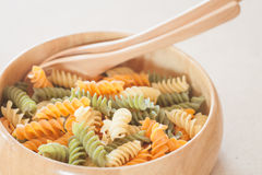 Raw fusilli pasta on wooden bowl Stock Image