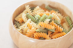 Raw fusilli pasta on wooden bowl Stock Photo