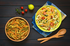 Raw Fusilli or Rotini Pasta and Vegetarian Pasta Salad. Overhead shot of raw fusilli pasta in wooden bowl and a plate of vegetarian pasta salad made of tricolor Royalty Free Stock Photography