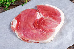 Raw gammon steak on crumpled paper with thyme Royalty Free Stock Photos