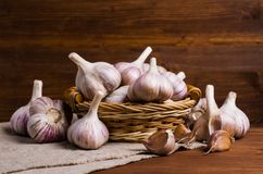 Raw garlic cloves. In a box on wooden background. Selective focus Royalty Free Stock Image