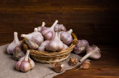 Raw garlic cloves. In a box on wooden background. Selective focus Stock Images