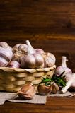 Raw garlic cloves. In a box on wooden background. Selective focus Royalty Free Stock Photos