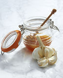 Raw Garlic Cloves and a Honey Jar Royalty Free Stock Images