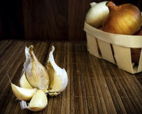 Raw garlic and onion on a wooden surface Stock Images