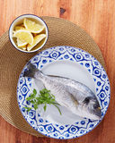 Raw gilt head bream. On a dish with lemon and parsley Royalty Free Stock Images