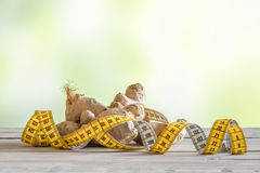 Raw ginger with measure tape. On a wooden table Royalty Free Stock Photos