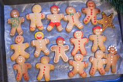 Raw gingerbread men with glaze on a baking sheet Stock Images