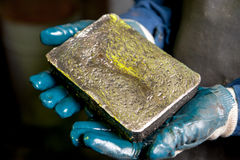 Raw gold ingot in the hands Royalty Free Stock Image