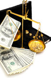Raw Gold And Money. Gold nuggets in the pan of a balance scale with many fifty and hundred dollar bills showing the value of both Stock Photos