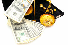 Raw Gold And Money. Gold nuggets in the pan of a balance scale with many fifty and hundred dollar bills showing the value of both stock image