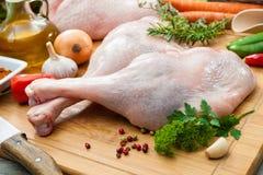 Raw goose legs on cutting board Stock Image