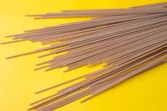 Raw grain pasta on yellow background. Flat spaghetti.Top view royalty free stock image