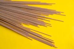 Raw grain pasta on yellow background. Flat spaghetti.Top view stock photos