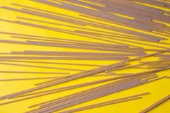 Raw grain pasta on yellow background. Flat spaghetti.Top view royalty free stock photo