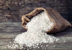Raw grains of white rice in burlap bag on wooden background Royalty Free Stock Image