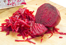 Raw grated beets. On a wooden board Royalty Free Stock Image