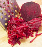 Raw grated beets. On a wooden board Royalty Free Stock Photos