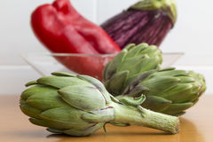 Raw green artichokes and other vegetables in a bowl behind Stock Photo