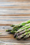 Raw green asparagus bunch on wooden table. Copy space Stock Images