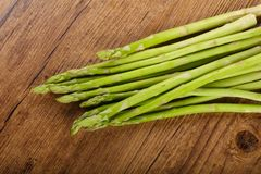 Raw green asparagus. Heap on the wood background Stock Image