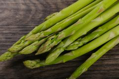 Raw green asparagus. Heap on the wood background Stock Photo
