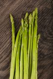 Raw green asparagus. Heap on the wood background Royalty Free Stock Photos