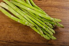 Raw green asparagus. Heap on the wood background Stock Photos