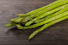 Raw green asparagus. Heap on the wood background Stock Photography