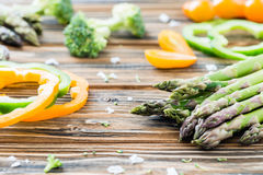 Raw green asparagus, pepper slices and broccoli . Wooden table. Raw green asparagus, green pepper slices and broccoli . Wooden table. Selective focus Royalty Free Stock Images