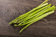 Raw green asparagus. Heap on the wood background Royalty Free Stock Photography