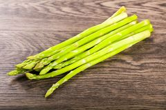 Raw green asparagus. Heap on the wood background Royalty Free Stock Images