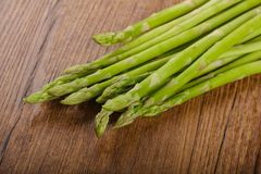 Raw green asparagus. Heap on the wood background Royalty Free Stock Photo