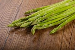 Raw green asparagus. Heap on the wood background Royalty Free Stock Image