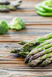 Raw green asparagus and veggies on wooden table. Selective focus. Raw green asparagus, green pepper slices, broccoli. Fresh ingredients. Wooden table. Selective Stock Image
