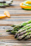 Raw green asparagus and veggies on wooden table. Selective focus. Raw green asparagus, green pepper slices, cherry tomatoes. Fresh ingredients. Wooden table Stock Image