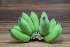 Raw green bananas on wooden background. Raw green bananas on wooden background, Unripe, fruit Royalty Free Stock Photo